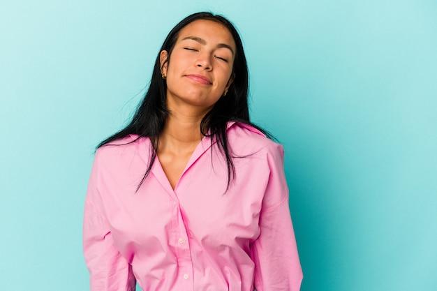 Jonge venezolaanse vrouw geïsoleerd op blauwe achtergrond lacht en sluit de ogen, voelt zich ontspannen en gelukkig.