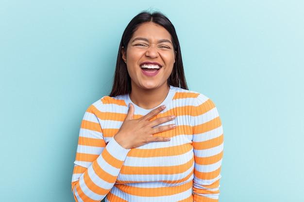 Jonge venezolaanse vrouw geïsoleerd op blauwe achtergrond lacht hardop terwijl ze de hand op de borst houdt.