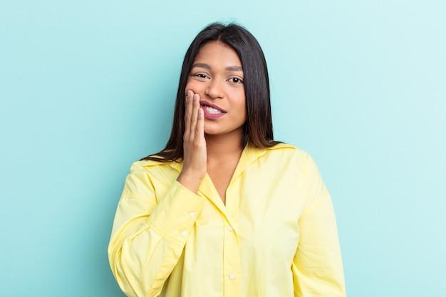 Jonge venezolaanse vrouw geïsoleerd op blauwe achtergrond met een sterke tandenpijn, kiespijn.