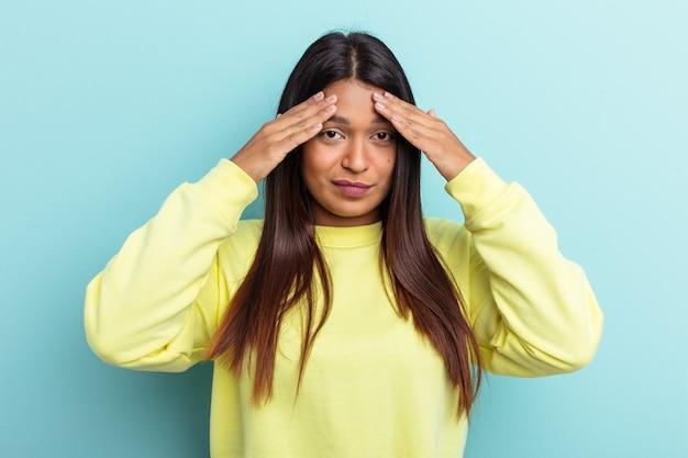 Jonge venezolaanse vrouw geïsoleerd op blauwe achtergrond met hoofdpijn, aanraken van de voorkant van het gezicht.