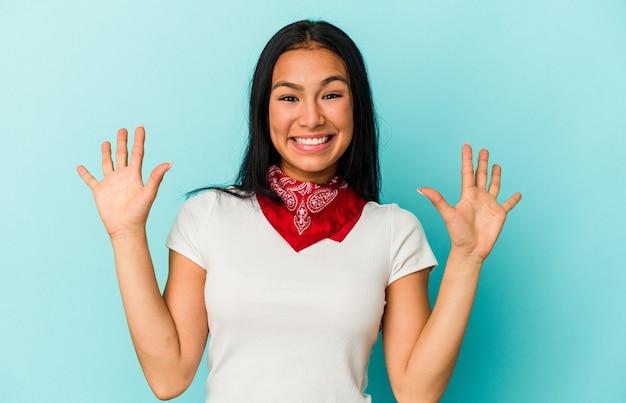 Jonge venezolaanse vrouw geïsoleerd op blauwe achtergrond met nummer tien met handen.