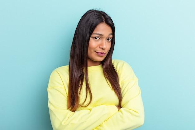 Jonge venezolaanse vrouw geïsoleerd op blauwe achtergrond ongelukkig in de camera kijken met sarcastische uitdrukking.
