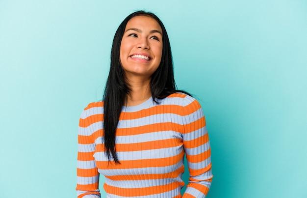 Jonge venezolaanse vrouw geïsoleerd op blauwe achtergrond ontspannen en gelukkig lachen, nek uitgerekt met tanden.
