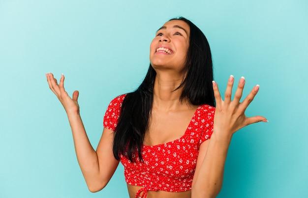 Jonge venezolaanse vrouw geïsoleerd op blauwe achtergrond schreeuwend naar de hemel, opzoeken, gefrustreerd.