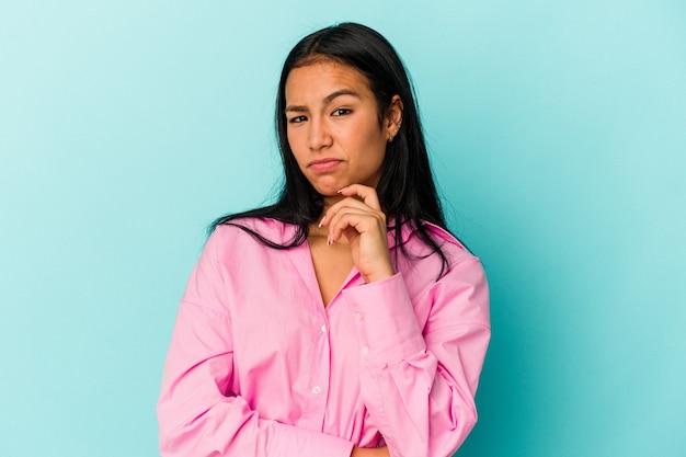 Jonge venezolaanse vrouw geïsoleerd op blauwe muur denkend en opzoekend, reflecterend, nadenkend, een fantasie hebbend.