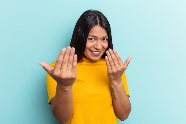 Jonge venezolaanse vrouw geïsoleerd op een blauwe achtergrond die met de vinger naar je wijst alsof uitnodigend dichterbij komt.