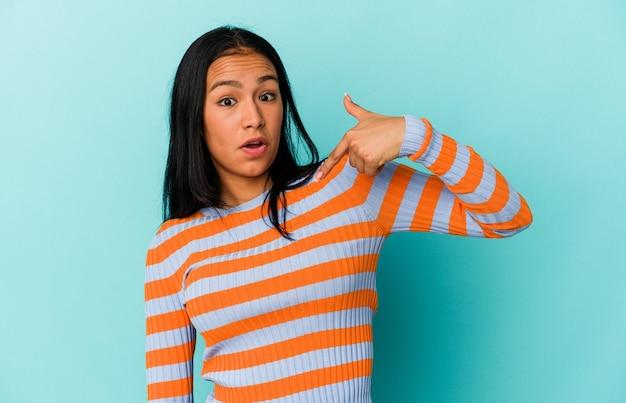 Jonge venezolaanse vrouw geïsoleerd op een blauwe achtergrond persoon die met de hand wijst naar een ruimte voor een shirtkopie, trots en zelfverzekerd