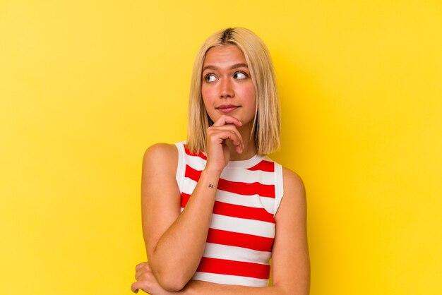 Jonge venezolaanse vrouw geïsoleerd op gele achtergrond denken en opzoeken, reflecterend zijn, nadenken, een fantasie hebben.