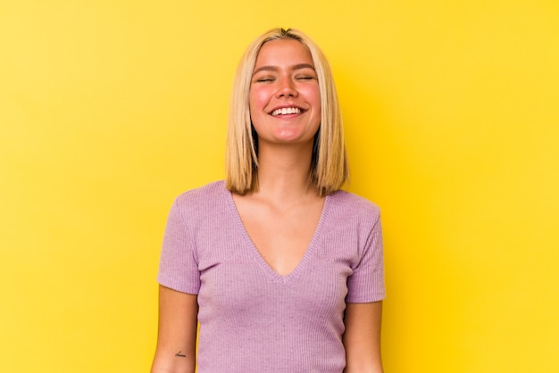 Jonge venezolaanse vrouw geïsoleerd op gele achtergrond lacht en sluit de ogen, voelt zich ontspannen en gelukkig.