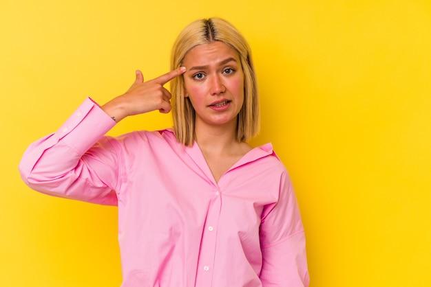 Jonge venezolaanse vrouw geïsoleerd op gele achtergrond met een teleurstelling gebaar met wijsvinger.