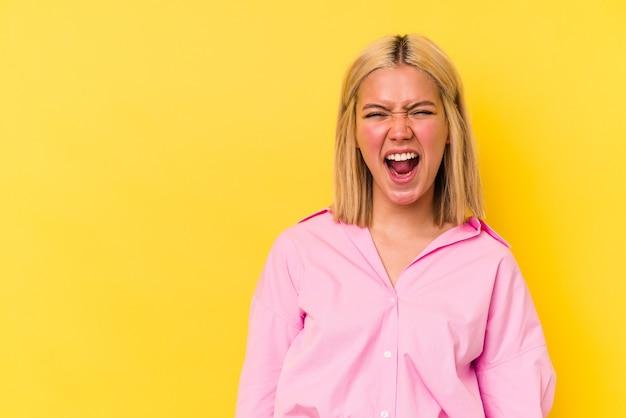 Jonge venezolaanse vrouw geïsoleerd op gele achtergrond schreeuwen erg boos, woede concept, gefrustreerd.