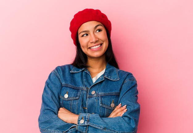 Jonge venezolaanse vrouw geïsoleerd op roze achtergrond glimlachend zelfverzekerd met gekruiste armen.