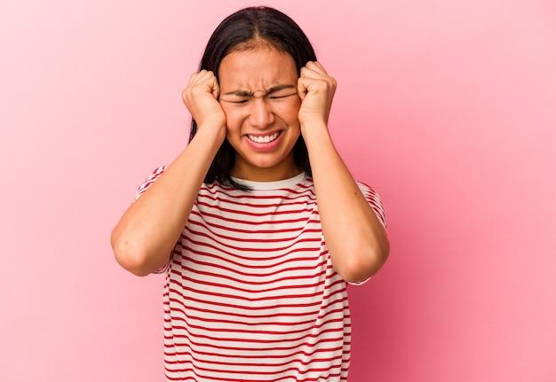 Jonge venezolaanse vrouw geïsoleerd op roze achtergrond huilen, ongelukkig met iets, pijn en verwarring concept.