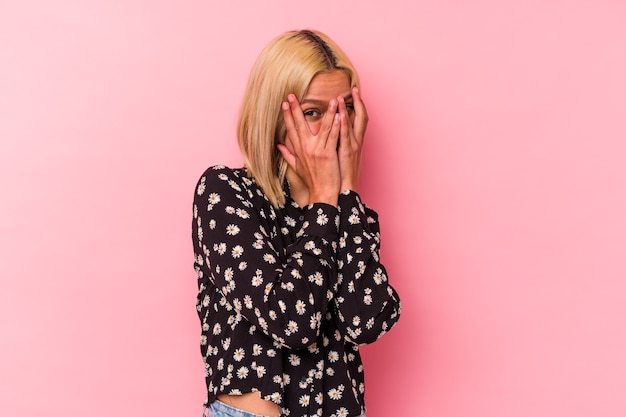 Jonge venezolaanse vrouw geïsoleerd op roze achtergrond knipperen door vingers bang en nerveus.