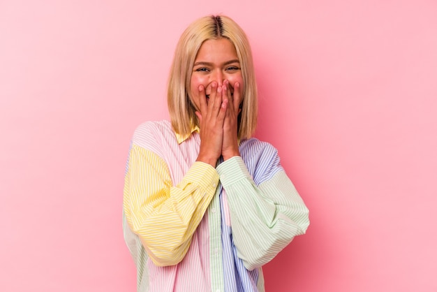 Jonge venezolaanse vrouw geïsoleerd op roze achtergrond lachen om iets, mond bedekken met handen.