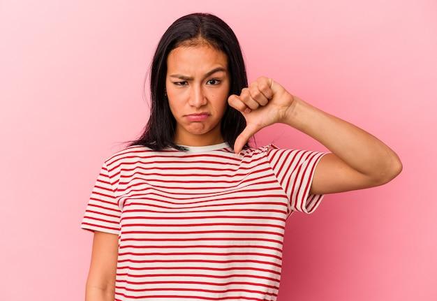 Jonge venezolaanse vrouw geïsoleerd op roze achtergrond met duim omlaag, teleurstelling concept.