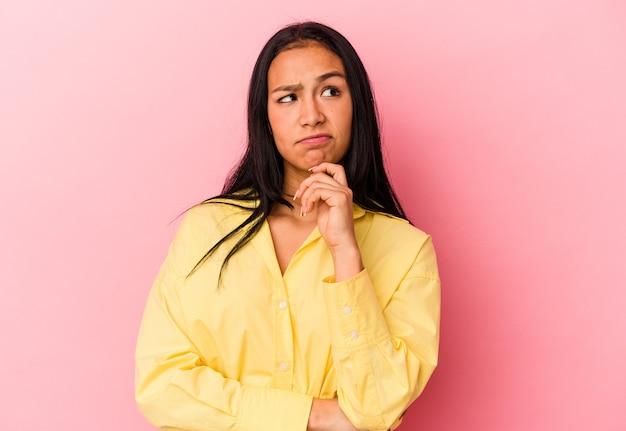 Jonge venezolaanse vrouw geïsoleerd op roze achtergrond zijwaarts kijkend met twijfelachtige en sceptische uitdrukking.
