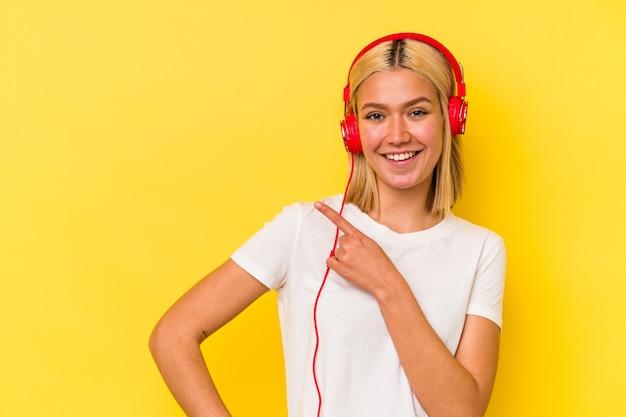 Jonge venezolaanse vrouw luisteren muziek geïsoleerd op gele achtergrond glimlachend en opzij wijzend, iets tonen op lege ruimte.