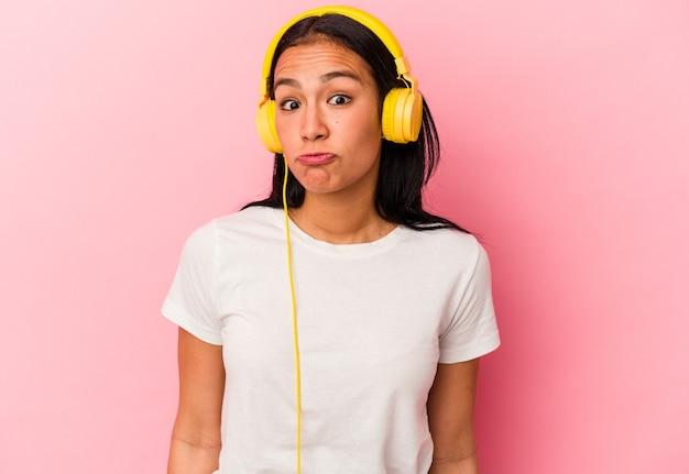 Jonge venezolaanse vrouw luisteren naar muziek geïsoleerd op roze achtergrond haalt schouders op en open ogen verward.