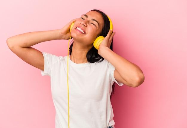 Jonge venezolaanse vrouw luisteren naar muziek geïsoleerd op roze background