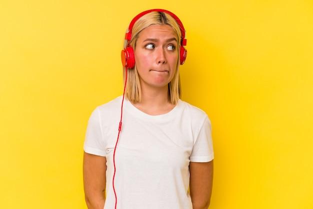 Jonge venezolaanse vrouw luistert naar muziek geïsoleerd op gele achtergrond verward, voelt zich twijfelachtig en onzeker.