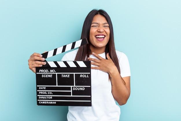 Jonge venezolaanse vrouw met een filmklapper geïsoleerd op blauwe achtergrond lacht hardop terwijl ze de hand op de borst houdt.