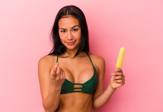 Jonge venezolaanse vrouw met een ijsje geïsoleerd op een roze achtergrond, wijzend met de vinger naar je alsof uitnodigend dichterbij komt.