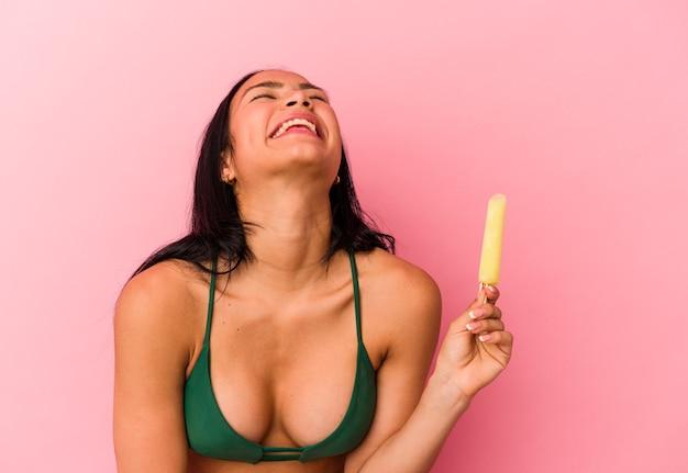 Jonge venezolaanse vrouw met een ijsje geïsoleerd op roze background