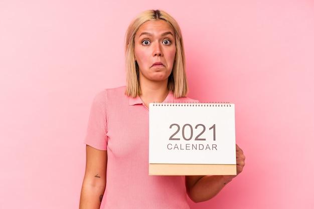 Jonge venezolaanse vrouw met een kalender geïsoleerd op roze achtergrond haalt schouders op en open ogen verward.