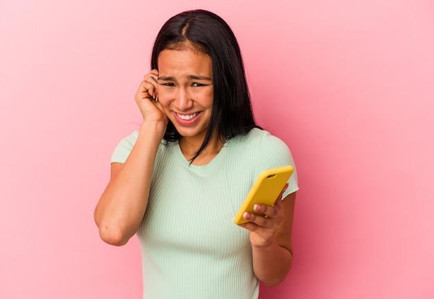Jonge venezolaanse vrouw met een mobiele telefoon geïsoleerd op een roze achtergrond die oren bedekt met handen.