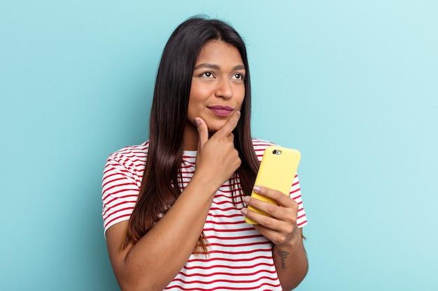 Jonge venezolaanse vrouw met mobiele telefoon geïsoleerd op blauwe achtergrond zijwaarts kijkend met twijfelachtige en sceptische uitdrukking.