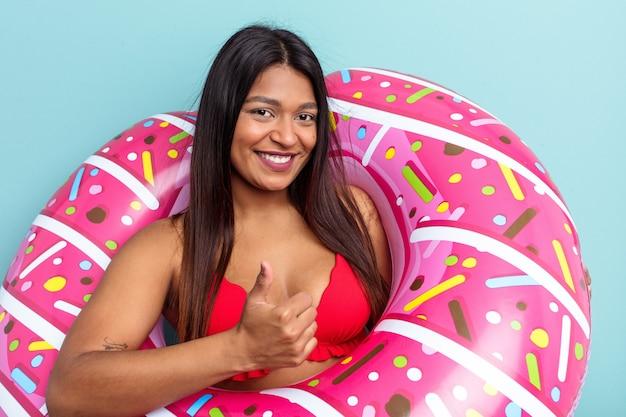 Jonge venezolaanse vrouw met opblaasbare donut geïsoleerd op blauwe achtergrond glimlachend en duim omhoog