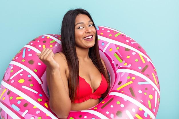 Jonge venezolaanse vrouw met opblaasbare donut geïsoleerd op blauwe achtergrond wijst met duimvinger weg, lachend en zorgeloos.