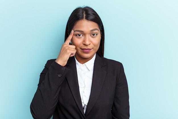 Jonge venezolaanse zakenvrouw geïsoleerd op blauwe achtergrond wijzende tempel met vinger, denken, gericht op een taak.