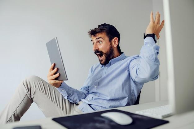 Jonge verbaasd bebaarde man gekleed business casual zitten in kantoor en kijken naar tablet.