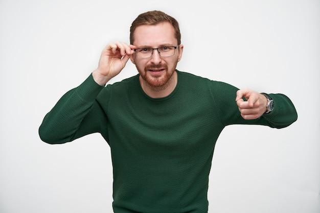 Jonge verbaasd brunette bebaarde man houdt zijn bril met opgeheven hand en wijst met wijsvinger, fronsend gezicht terwijl poseren