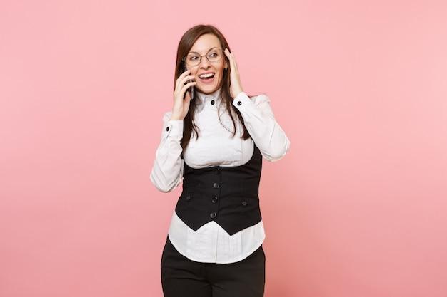 Jonge verbaasd succesvolle zakenvrouw in glazen praten op mobiele telefoon houden hand in de buurt van hoofd geïsoleerd op pastel roze achtergrond. dame baas. prestatie carrière rijkdom. kopieer ruimte voor advertentie.
