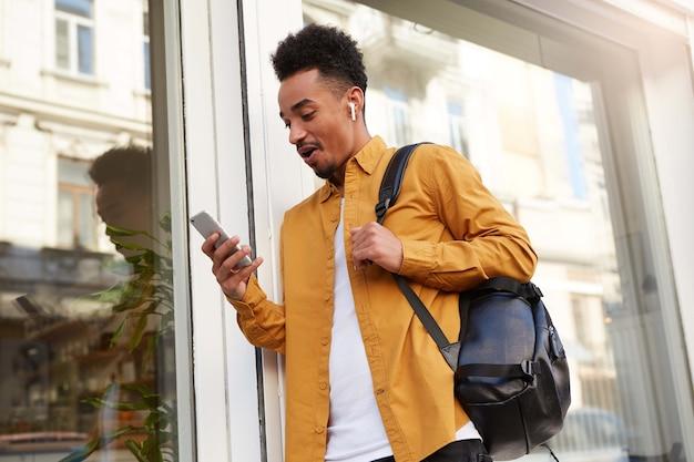 Jonge, verbaasde, donkere man in een geel overhemd, loopt over straat, houdt telefoon vast en leest ongelooflijk nieuws, met wijd open mond en ogen, ziet er versuft uit.