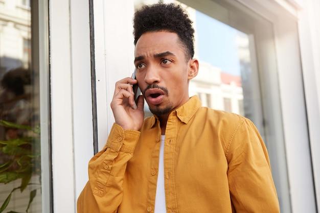 Jonge, verbaasde, donkere man met een donkere huidskleur in een geel overhemd, spreekt aan de telefoon met zijn vrienden en loopt met een geschokte uitdrukking op straat.
