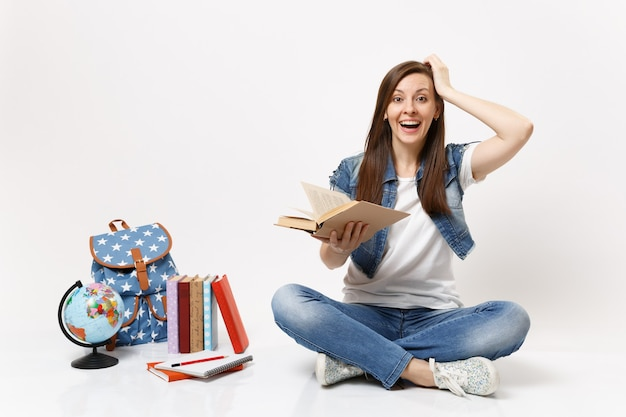Jonge verbaasde lachende studente in denimkleren houdt de hand bij het houden van de boekhouding in de buurt van het hoofd, zit in de buurt van de wereldbol, rugzak, geïsoleerde schoolboeken