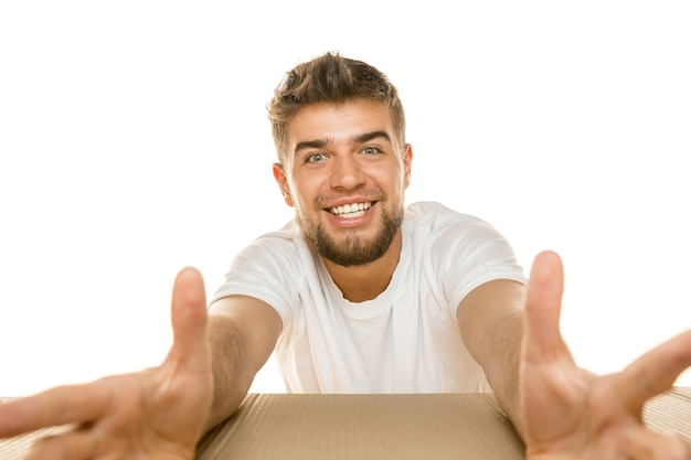 Jonge verbaasde man die het grootste postpakket opent dat op een witte muur is geïsoleerd