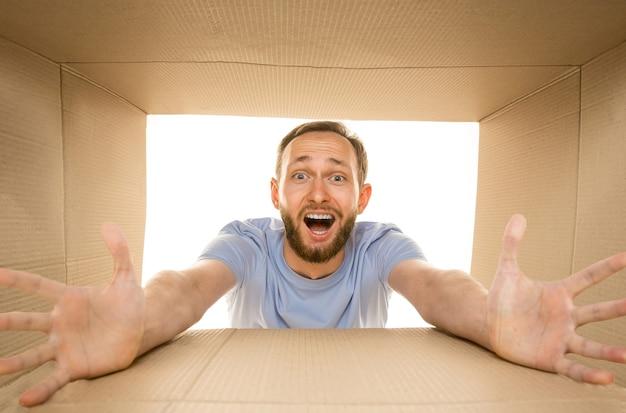Jonge verbaasde man die het grootste postpakket opent dat op wit wordt geïsoleerd. geschokt mannelijk model bovenop kartonnen doos