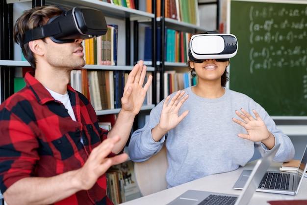 Jonge verbaasde man en vrouw in vr-headsets met virtuele ervaring tijdens les op de universiteit