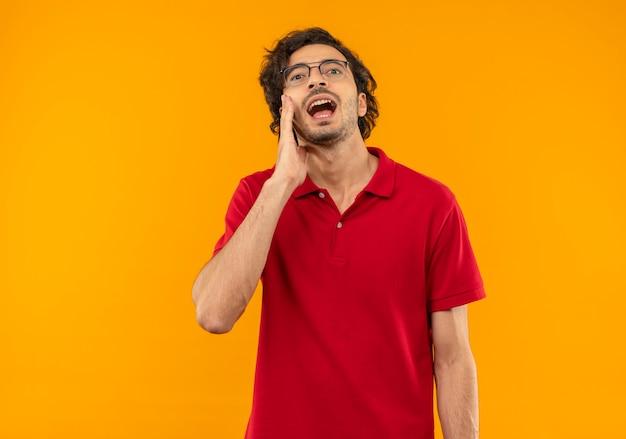 Jonge verbaasde man in rood shirt met optische bril legt hand op gezicht en doet alsof hij iemand belt die op een oranje muur is geïsoleerd