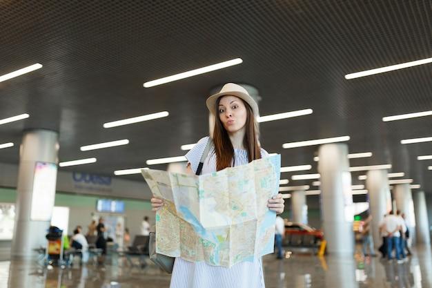 Jonge verbaasde reizigerstoeristenvrouw in hoed met papieren kaart, zoekend naar route tijdens het wachten in de lobbyhal op de internationale luchthaven