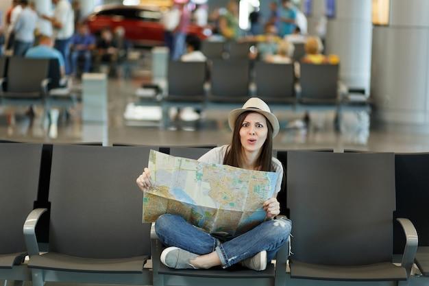 Jonge verbaasde reizigerstoeristenvrouw met gekruiste benen houdt papieren kaart vast, zoekt route in lobbyhal op internationale luchthaven
