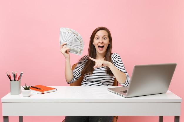 Jonge verbaasde vrouw die wijsvinger wijst op bundel veel dollars, contant geld werkt op kantoor aan een wit bureau met pc-laptop