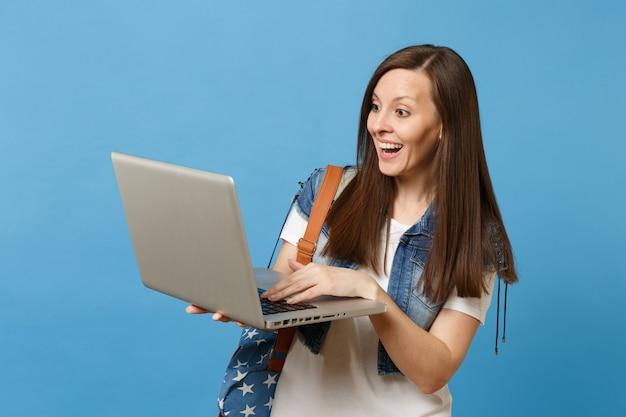 Jonge verbaasde vrouw student in denim kleding met rugzak houden en werken op laptop pc-computer geïsoleerd op blauwe achtergrond. onderwijs op de middelbare school. kopieer ruimte voor advertentie.