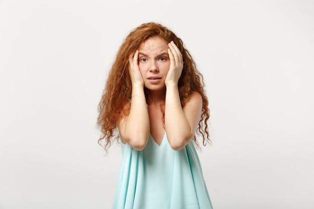 Jonge verbijsterde gepreoccupeerde roodharige vrouw in casual lichte kleding poseren geïsoleerd op een witte achtergrond in de studio. mensen oprechte emotie levensstijl concept. bespotten kopie ruimte. handen op de wangen leggen.
