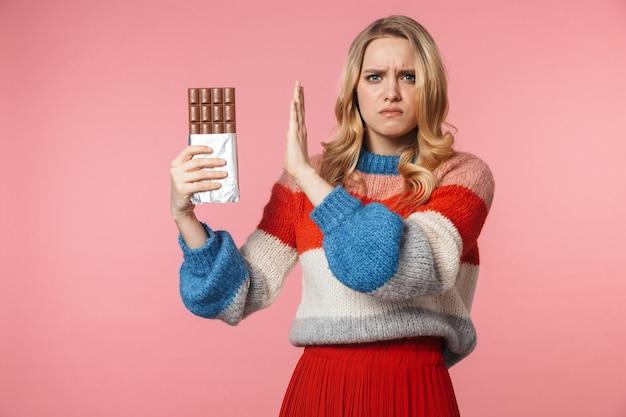 Jonge verdrietig nerveus mooie vrouw poseren geïsoleerd over roze muur met chocolade maken stop gebaar